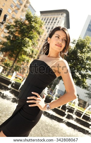 Profile of attractive woman in Black outfit with hands on hips leaning back. - stock photo