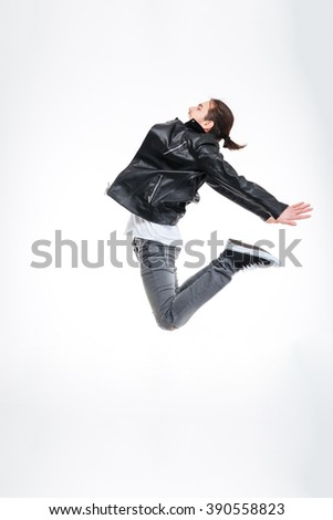 Profile of attractive young man in black leather jacket jumping high over white background - stock photo