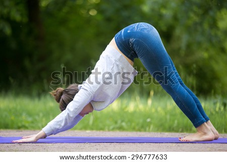 Profile of beautiful sporty young woman working out on street, doing stretching exercises on blue mat in park alley, standing in downward facing dog pose, surya namaskar, full length - stock photo
