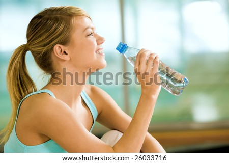 Profile of beautiful woman going to drink some water fron plastic bottle after workout - stock photo