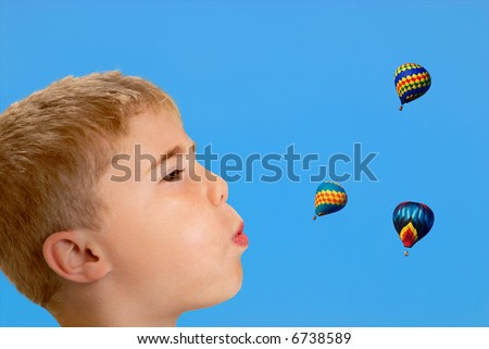 Profile of boy blowing at hot air balloons in sky - stock photo