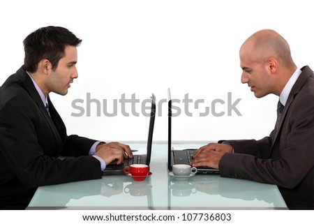 Profile of businessmen working at their laptops - stock photo