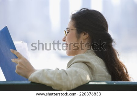 Profile of businesswoman reading papers - stock photo
