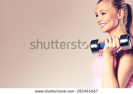 Profile of fit and healthy young woman smiling and holding dumbbell to shoulder. - stock photo
