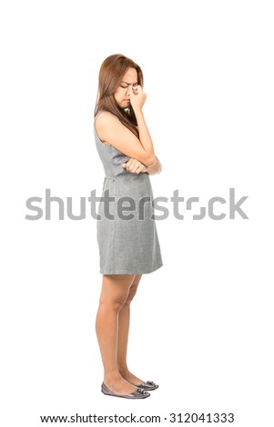 Profile of frowning migraine sufferer Asian woman in sleeveless gray dress holding bridge of nose suffering from sinus congestion or headache. Thai national of Chinese origin. Full length - stock photo