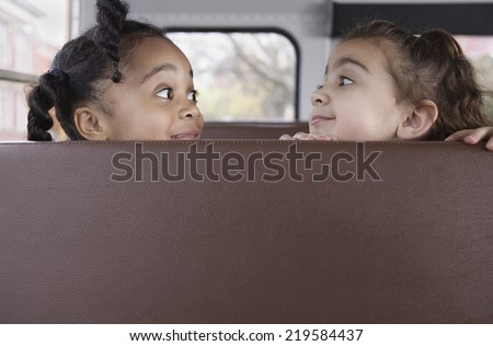 Profile of girls on school bus - stock photo