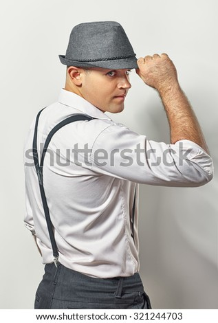 Profile of handsome gentleman in hat on white - stock photo