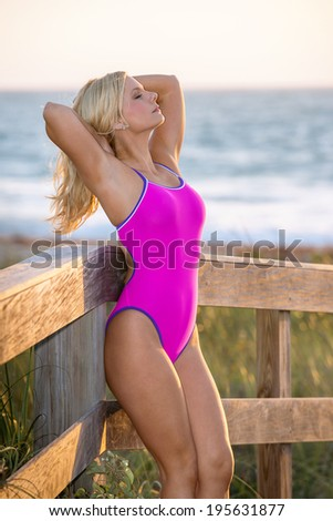 profile of lovely blond female swimsuit model at a florida beach at sunrise - stock photo
