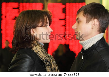 Profile of man and woman in leather jacket look to each other in eye on background of flight timetable - stock photo