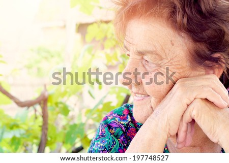Profile of positive old female with smile on her face - stock photo