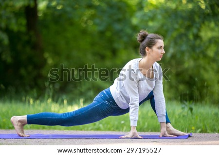Profile of serene beautiful sporty young woman working out on blue mat on the street in park alley, doing stretching exercises, easy variation of Utthan Pristhasana (Lizard Pose), full length - stock photo