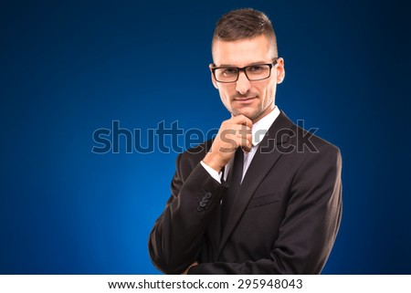 Profile of serious businessman in black business suit. Confident man with glasses on touching his chin and smiling on blue background. - stock photo