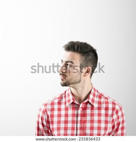 Profile of serious young bearded man looking away over gray background. - stock photo
