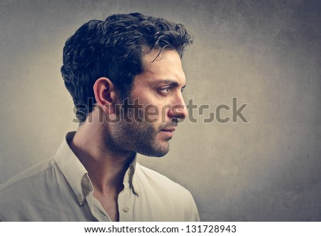 profile of serious young man on gray background - stock photo