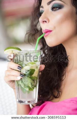 Profile of sexual cute young woman with curly hair and bright makeup drinking alcoholic mojito cocktail from mint soda light rum and lime with straw, vertical picture - stock photo