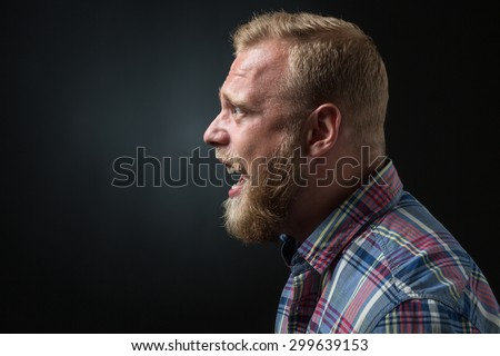 Profile of shouting bearded man isolated on black. Blond man in plaid shirt screaming because of annoyance. - stock photo
