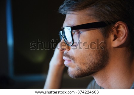 Profile of thoughtful handsome young man with bristle in glasses sitting and thinking - stock photo