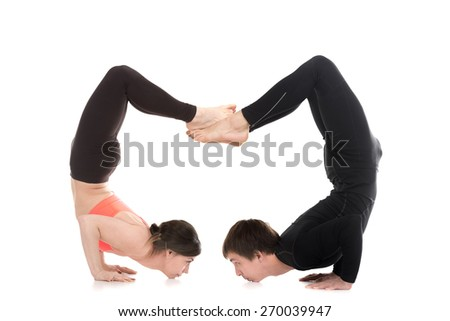 Profile of two sporty people doing backbend handstand, yogi couple standing in yoga chin balance asana ganda bherundasana, fierce bird posture on white background - stock photo
