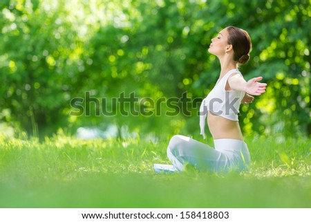 Profile of woman sitting in lotus position with outstretched arms. Concept of healthy lifestyle and relaxation - stock photo