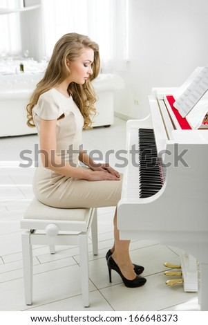 Profile of woman sitting on bench and looking at piano. Concept of music and art - stock photo