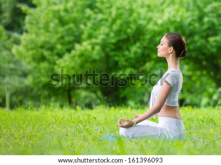 Profile of woman with eyes closed who sits in asana position zen gesturing. Concept of healthy lifestyle and relaxation - stock photo