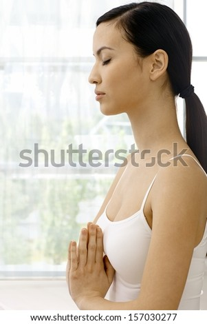 Profile of young attractive woman practicing yoga, relaxing eyes closed. - stock photo