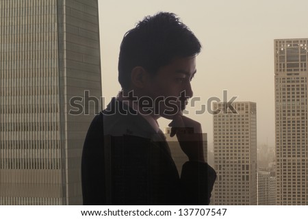 Profile of young businessman contemplating, double exposure of cityscape, Beijing - stock photo