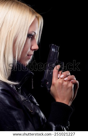 Profile of young female detective with gun isolated on black background. - stock photo