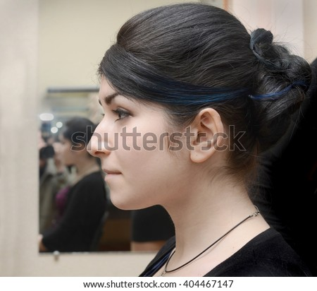 profile of young girl with black hair, aquiline nose - stock photo