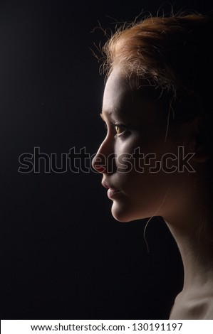 profile of young pensive woman with red hairs on black background - stock photo