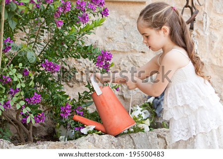 Profile portrait of a beautiful young child girl holding a watering can, watering the plants in her holiday home garden, focused outdoors. Kid helping with home duties while on vacation, lifestyle. - stock photo