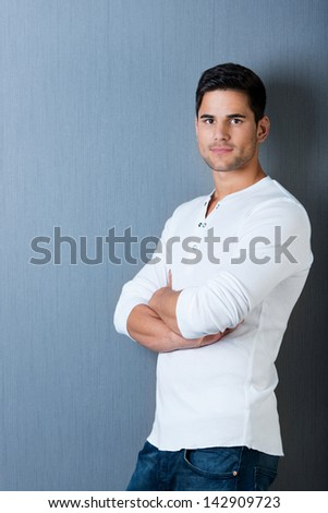 Profile portrait of a handsome male standing leaning on the wall with arms crossed, isolated on blue background. - stock photo
