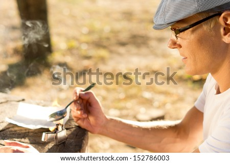 Profile portrait of a middle-aged man heating a dose of crack cocaine in a teaspoon in a park - stock photo