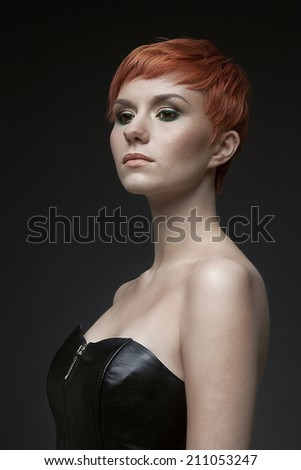 Profile portrait of  a stylish red-haired model with trendy hairstyle. Isolated on a dark background. - stock photo