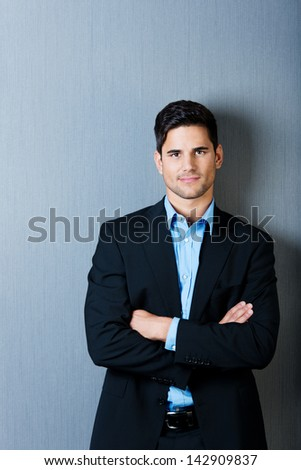 Profile portrait of a well dressed businessman standing with arms crossed, isolated on blue background. - stock photo