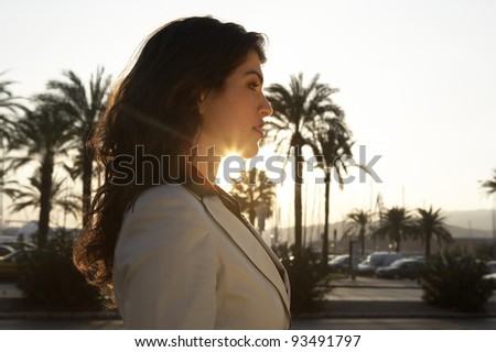 Profile portrait of a woman with sun rays filtering through her neck. - stock photo