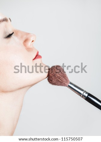 profile portrait of a womans face and a blush brush - stock photo