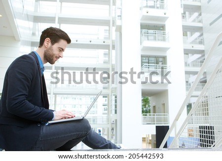 Profile portrait of a young man working on laptop indoors - stock photo