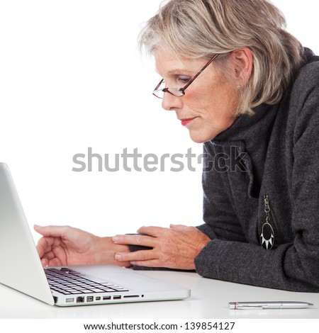 Profile portrait of an attractive senior woman working on a laptop leaning forwards to peer at something on the screen - stock photo