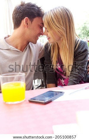 Profile portrait of attractive young couple on holiday being romantic and kissing while sitting at a coffee terrace bar drinking refreshments during a summer vacation. Love and relationships outdoors. - stock photo