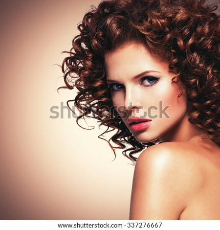 Profile portrait of beautiful young sexy woman with brunette curly hair looking at camera. - stock photo