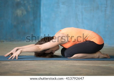Profile portrait of beautiful young woman dressed in bright sportswear enjoying yoga indoors. Yogi girl working out in grunge interior with blue wall. Doing Stretching exercise for back. Child Pose - stock photo