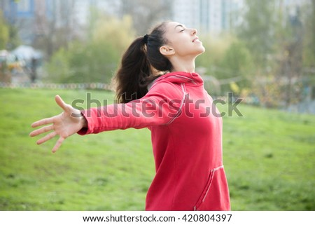 Profile portrait of happy sporty woman relaxing in park. Joyful female model relaxing, breathing fresh air outdoors with opened arms. Healthy active lifestyle concept - stock photo