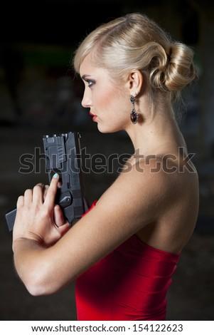 Profile portrait of Woman in retro look holding a gun - stock photo