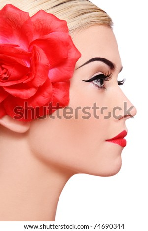 Profile portrait of young beautiful blond woman with red flower in hair, on white background - stock photo