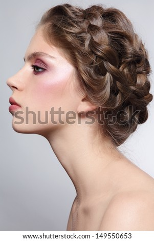 Profile portrait of young beautiful girl with braids hairdo - stock photo