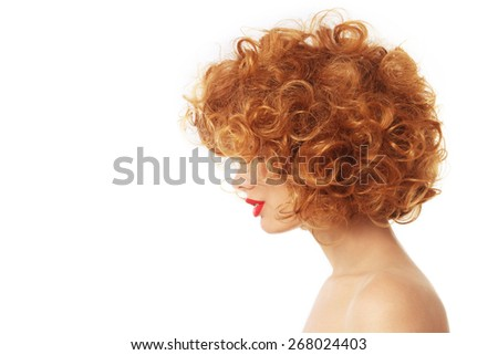 Profile portrait of young woman with beautiful red curly hair over white background - stock photo