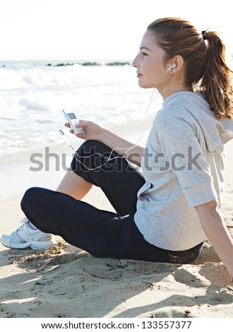 Profile portrait view of a young woman sitting on a fine sand beach shore, holding a music player and listening to music with her head phones being thoughtful. - stock photo