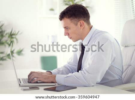 Profile shot of a  businessman working on his laptop in the office.He is wearing a blue  shirt and a black tie.Selective focus - stock photo