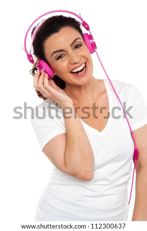Profile shot of a cheerful young beautiful lady enjoying music on her pink headphones - stock photo
